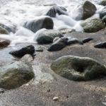 Wellen gleiten über Steine